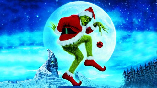 The Grinch posing in front of the moon holding a bauble
